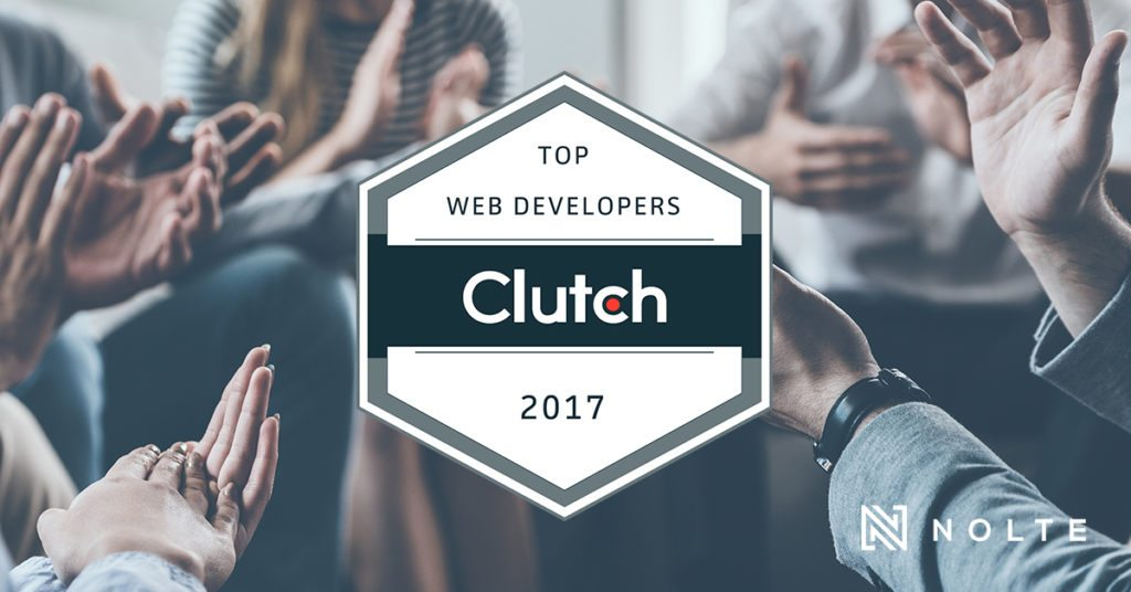 Group of people clapping altogether behind clutch badge for top web development 2017
