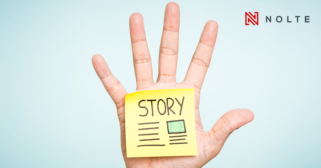 a yellow post-it sticked in an open hand with the word story written